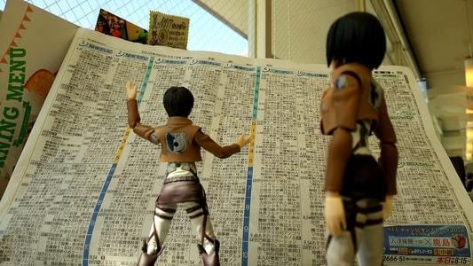 グラッチェガーデンズ桜山店 新聞のテレビ欄で進撃の巨人の放送時間を確認するエレンとミカサ